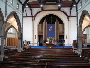 Trinity church interior from rear toward pulpit and Praying Hands embroidery