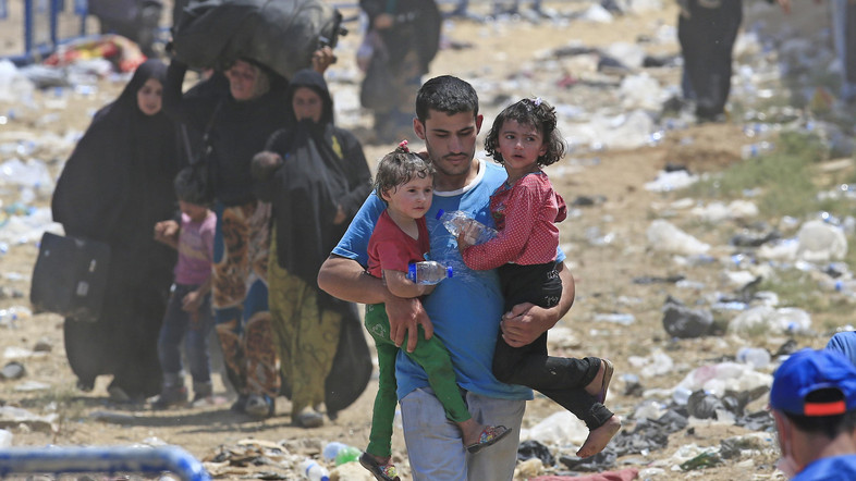 A Syrian refugee carrying children, walks in Turkey, in Akcakale, southeastern Turkey, as he and others flee intense fighting in northern Syria between Kurdish fighters and Islamic State militants, Monday, June 15, 2015. The flow of refugees came as Syrian Kurdish fighters closed in on the outskirts of a strategic Islamic State-held town on the Turkish border. (AP Photo/Lefteris Pitarakis)